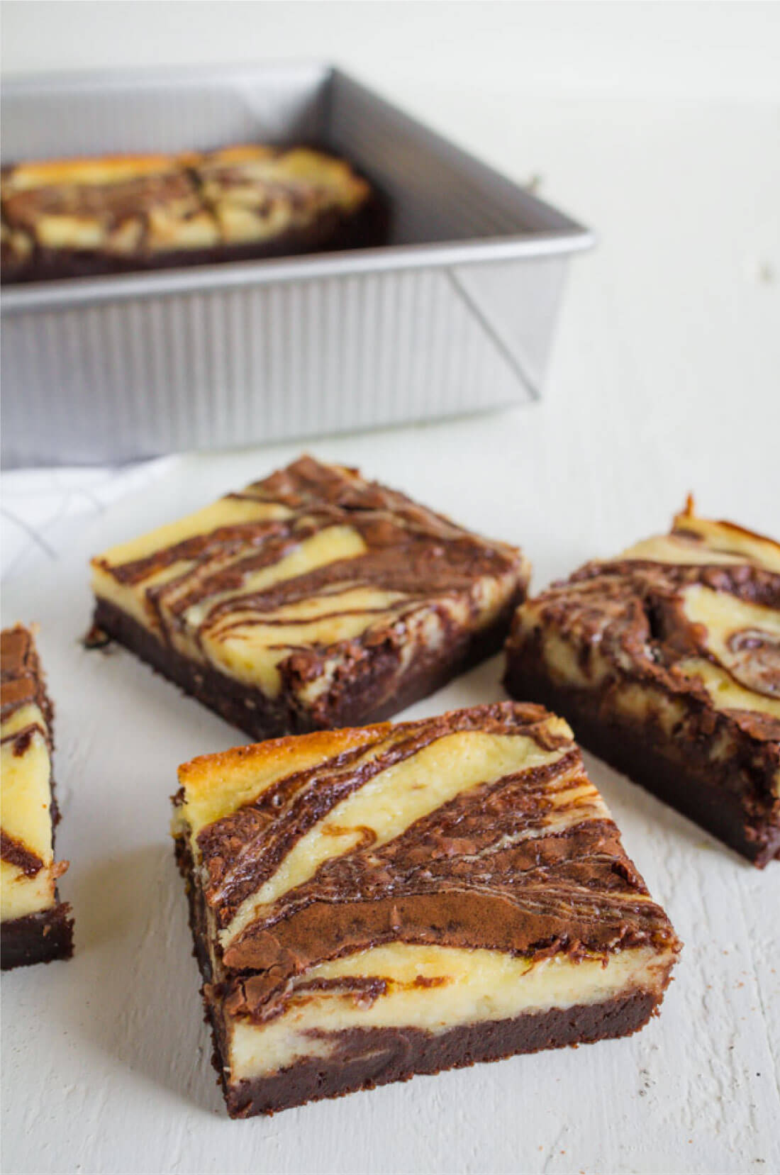 Cheesecake Brownies - they are delicious and simple and a fun take on regular brownies. Pan full of brownies and cut up.