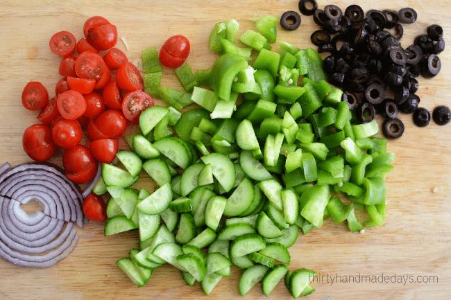Chop vegetables for greek pasta salad dressing
