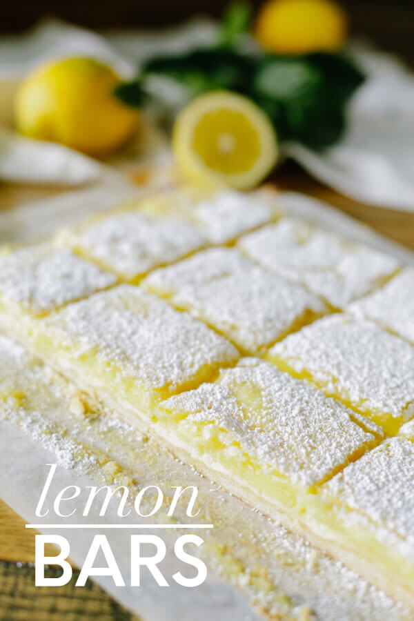 Lemon bars up close with lemons in the background